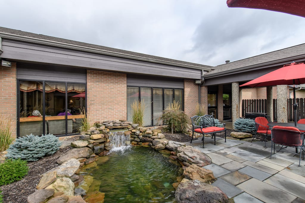 senior living patio and waterfall at The Inn at Belden Village