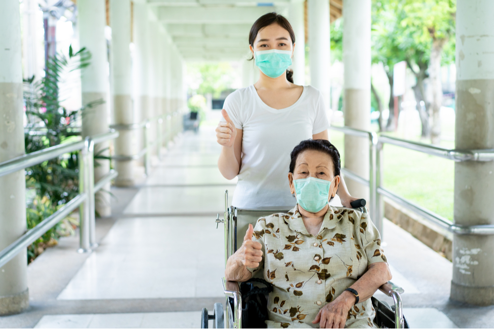 Masked assisted living resident and visitor