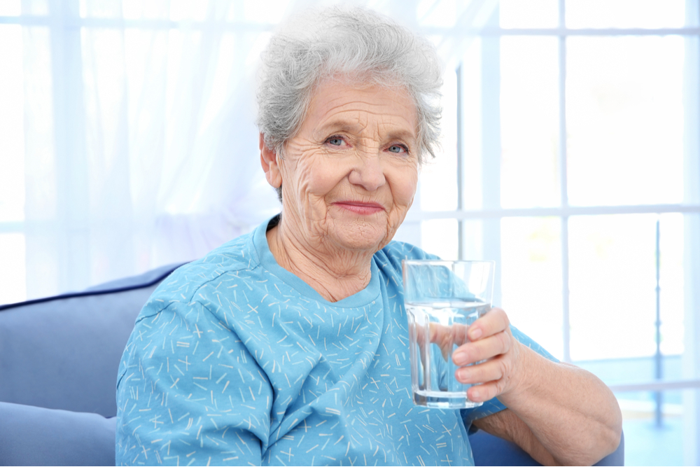 Senior woman drinking water staying hydrated